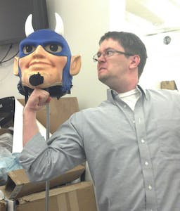 Kyle McKay, a marketing manager at Student Stores, poses with the head of the Duke Blue Devil mascot costume.