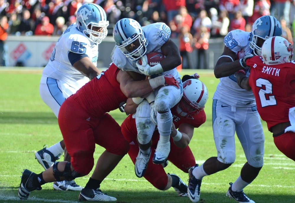 "<p><span class=""caps"">UNC</span> running back Giovani Bernard fights for extra yards against the Wolfpack defense in <span class=""caps"">UNC</span>&#8217;s 13-0 loss to NC State at Carter-Finley Stadium in Raleigh, NC. </p>"