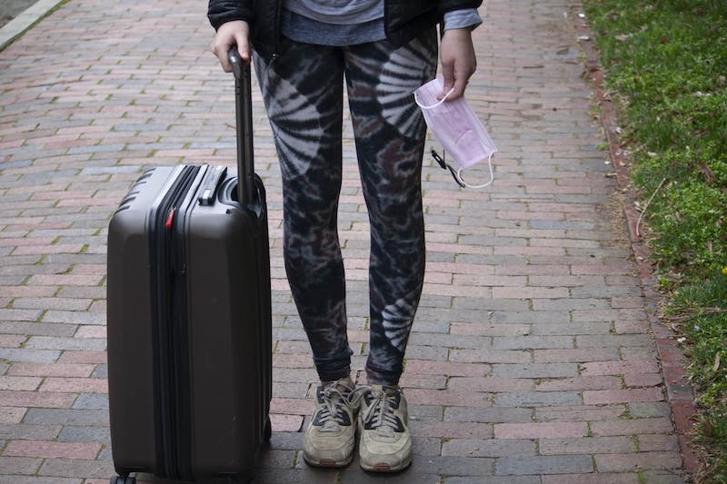DTH Photo Illustration. A UNC student holds a suitcase and a surgical mask on campus on Tuesday, March 3, 2020. Students are unsure how the coronavirus will affect their plans to study abroad.
