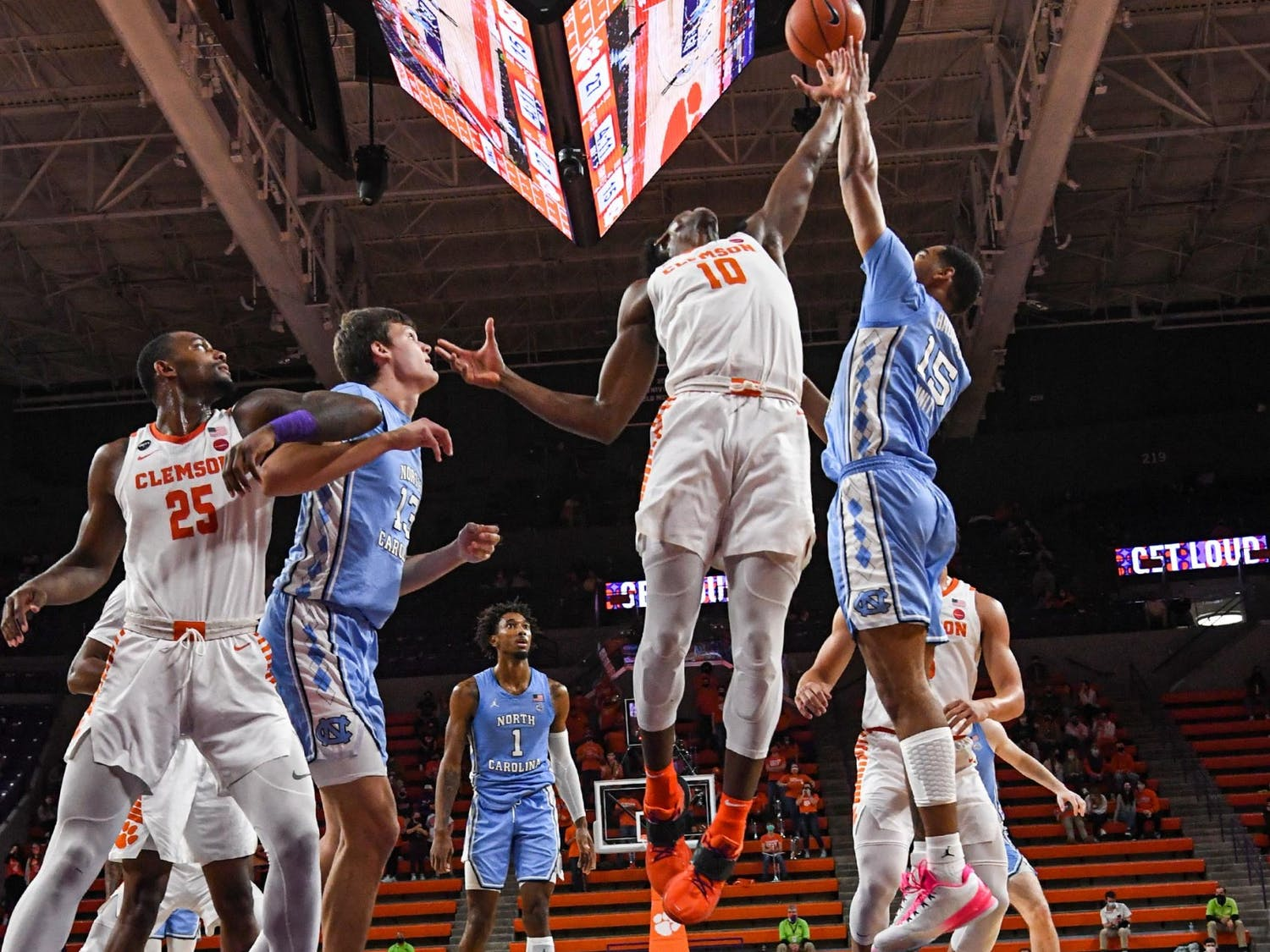 Clemson freshman guard Olivier-Maxence Prosper(10) and North Carolina forward Garrison Brooks(15) reach for a loose ball during the first half of a game at Littlejohn Coliseum on Feb. 2, 2021. Photo courtesy of Ken Ruinard.