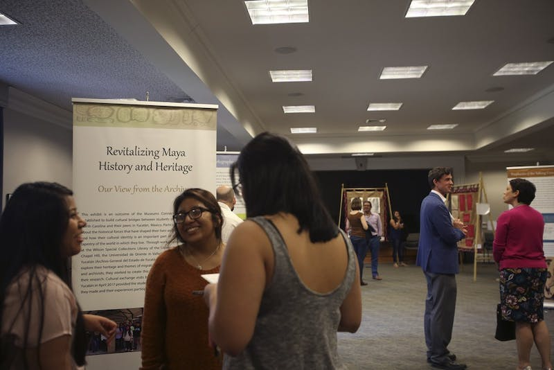People came to the reception of the Mayan exhibit curated by high schoolers from Morganton, NC and Mexico, displayed in the Wilson Special Collections Library on Friday, April 14.