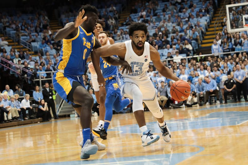 UNC first-year guard Jeremiah Francis (13) runs the ball past Pitt graduate forward Eric Hamilton (0) during a game in the Dean Smith Center on Wednesday, Jan. 8, 2020. The Tar Heels lost to the Panthers 65-73.
