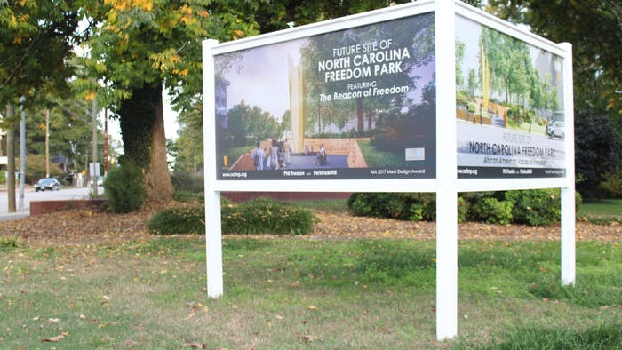 A sign indicates the future site of the Freedom Park at the corner of South Wilmington Street and East Lane Street in downtown Raleigh.