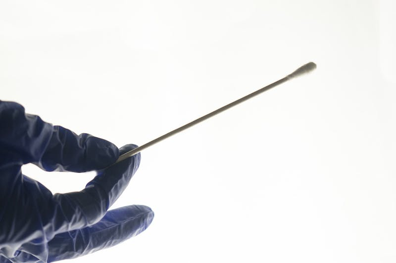 DTH Photo Illustration depicting a nasal swab used for COVID-19 testing.