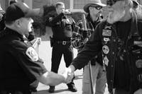A pro-Confederate protester shakes hands with UNC Police officer Timothy Tickle after Tickle explained to protesters the boundaries of UNC's campus. The pro-Confederate group then left campus. Photo courtesy of Daniel Hosterman.