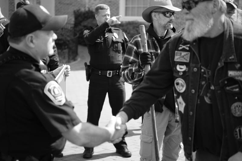 A pro-Confederate protester shakes hands with UNC Police officer Timothy Tickle after Tickle explained to protesters the boundaries of UNC's campus on March, 16, 2019.The pro-Confederate group then left campus. Photo courtesy of Daniel Hosterman.