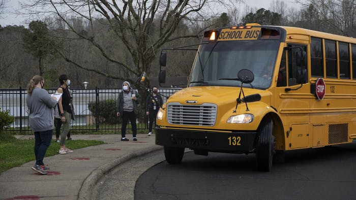 Frank Porter Graham Elementary faculty await students to depart the bus early in the morning on March 26, 2021. CHCCS have recently reopened in-person instruction, although many children are still learning virtually.