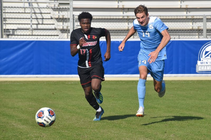 UNC senior Nils Bruening (14) and Louisville sophomore Elijah Amo (17) race to get obtain possession in the ACC championship game on Sunday, Nov. 11, 2018 at WakeMed Soccer Park. UNC lost to Louisville 0-1.