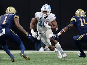 UNC graduate running back Ty Chandler (19) sprints by his opponents during UNC football's away game against Georgia Tech in the Mercedes-Benz Stadium in Atlanta, GA, on Sept. 25. Photo courtesy of UNC Athletic Communications.