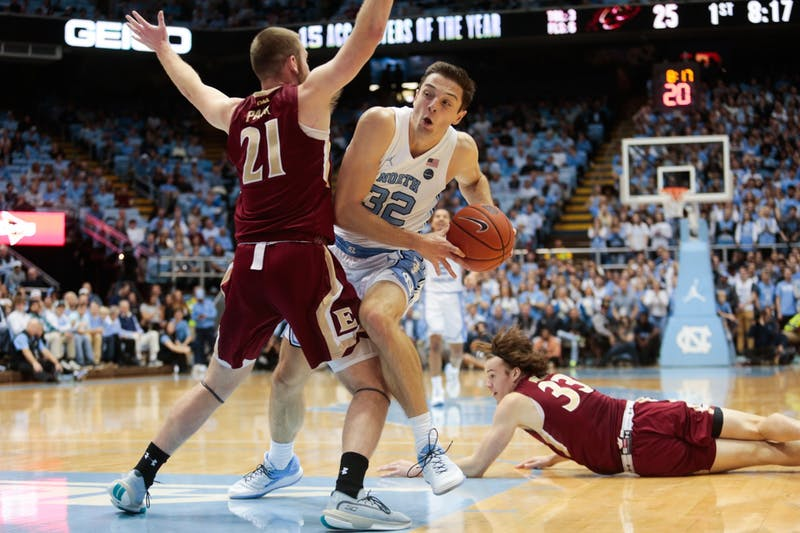 UNC graduate forward Justin Pierce (32) attempts an offensive drive past Elon sophomore guard Andy Pack (21) and junior forward Simon Wright (33) during a game in the Smith Center on Wednesday, Nov. 20, 2019. The Tar Heels beat the Phoenixes 75-61.