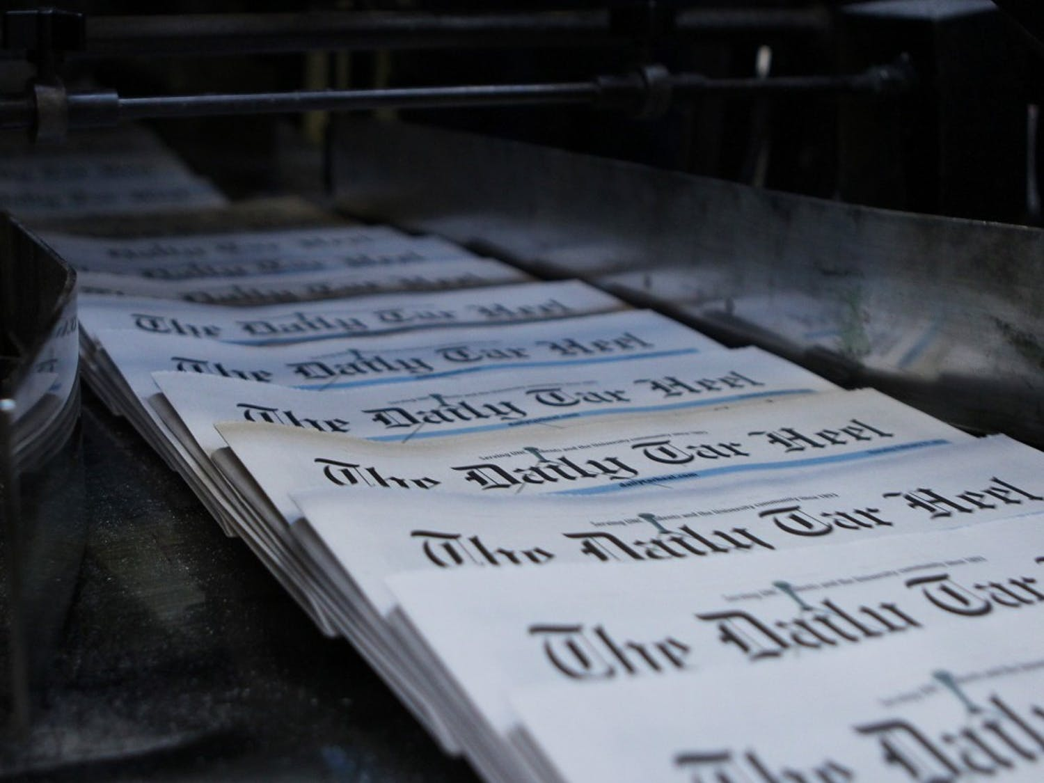 Newspapers come off the press to be bundled for delivery.