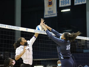 UNC graduate outside hitter Nia Robinson (18) blocks the ball during the UNC women's volleyball team's matchup against ECU on Sep. 4. The Tar Heels won in three sets, advancing their record to 6-0.