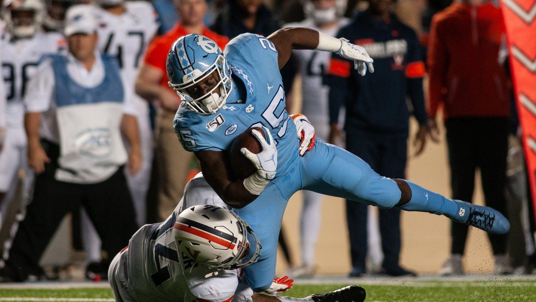 Virginia's Noah Taylor (14) tackles sophomore running back Javonte Williams (25) during the game in Kenan Memorial Stadium on Saturday, Nov. 2, 2019. UNC lost to Virginia 38-31.
