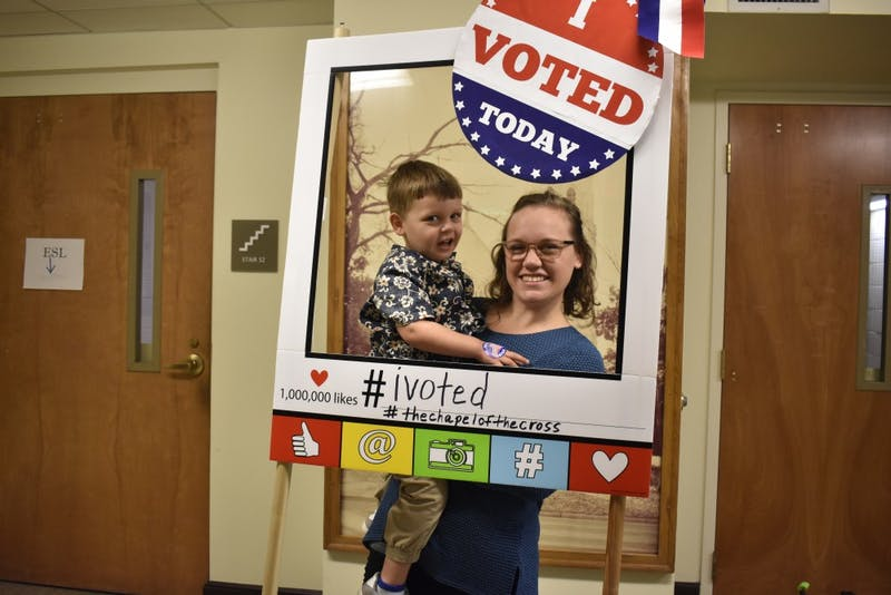 Melanie Unwin and her son take a picture together after she cast her vote at the Chapel of the Cross church at 304 E. Franklin St. on Oct. 23, 2018 helping voters register. The Chapel of the Cross severs as an early voter location close to the University of North Carolina at Chapel Hill's campus.