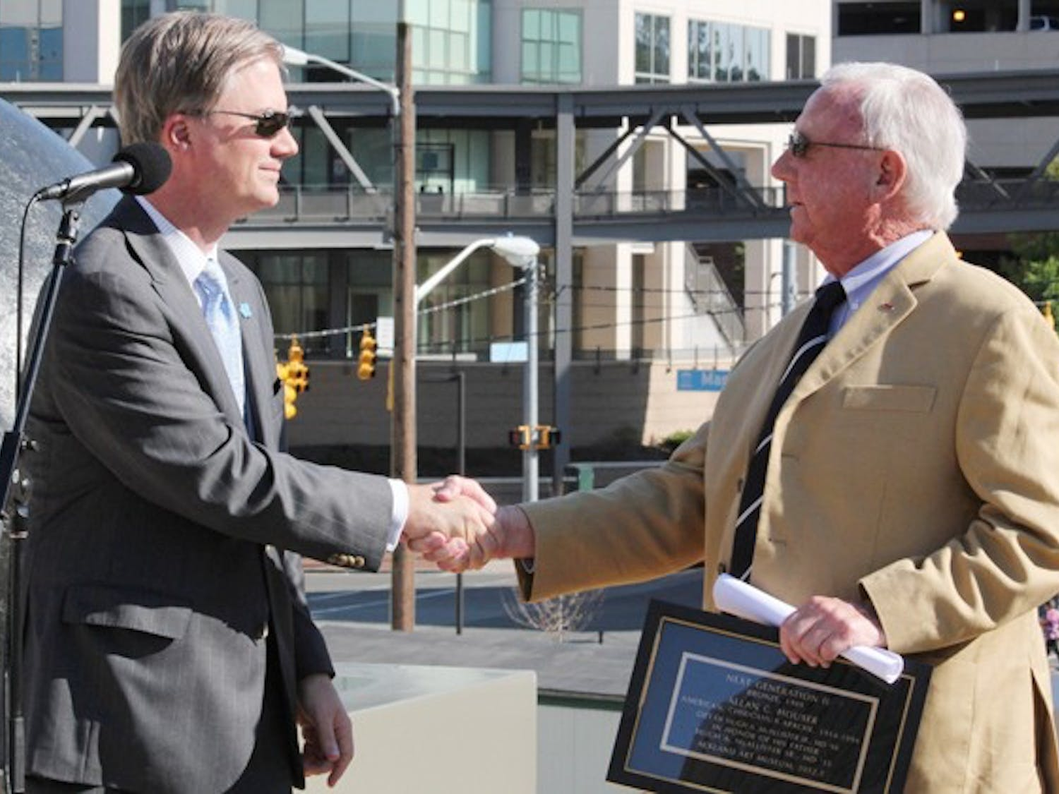 Holden Thorp shakes hands with UNC alumna Dr. Hugh A. McAllister Jr. who donated $10 million to UNC for the Ackland Art Museum  and the School of Medicine.