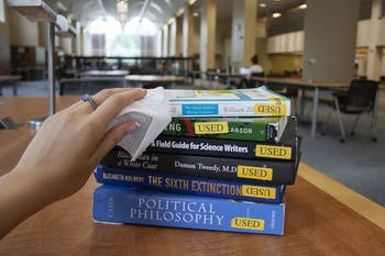 DTH Photo Illustration. A student wipes down books in Davis Library on Sunday, Aug. 16, 2020. UNC libraries are enforcing new protocols to prioritize the health and safety of library goers.