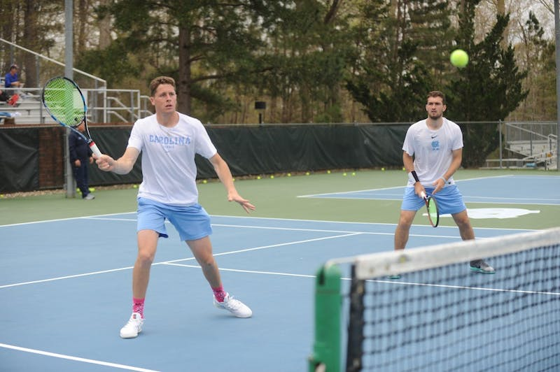 Senior Blaine Boyden (left) and junior William Blumberg (right) warm up before a match against Notre Dame on Sunday, April 7, 2019. UNC won 5-0.
