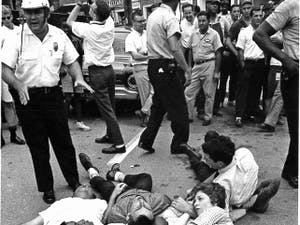 """Photo courtesy of Chapel Hill Public Library, from their book """"Courage in the Moment. The Civil Rights Struggle 1961-1964"""" photographed by Jim Wallace. Protestors had to agree to practice nonviolent resistance by neither assisting or resisting arrest, here the demonstrators are lying on Franklin Street, according to the book."""