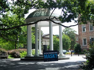 A sign reminding students and visitors to wear a mask sits near the Old Well on UNC's campus on Thursday, Aug. 13 2020.