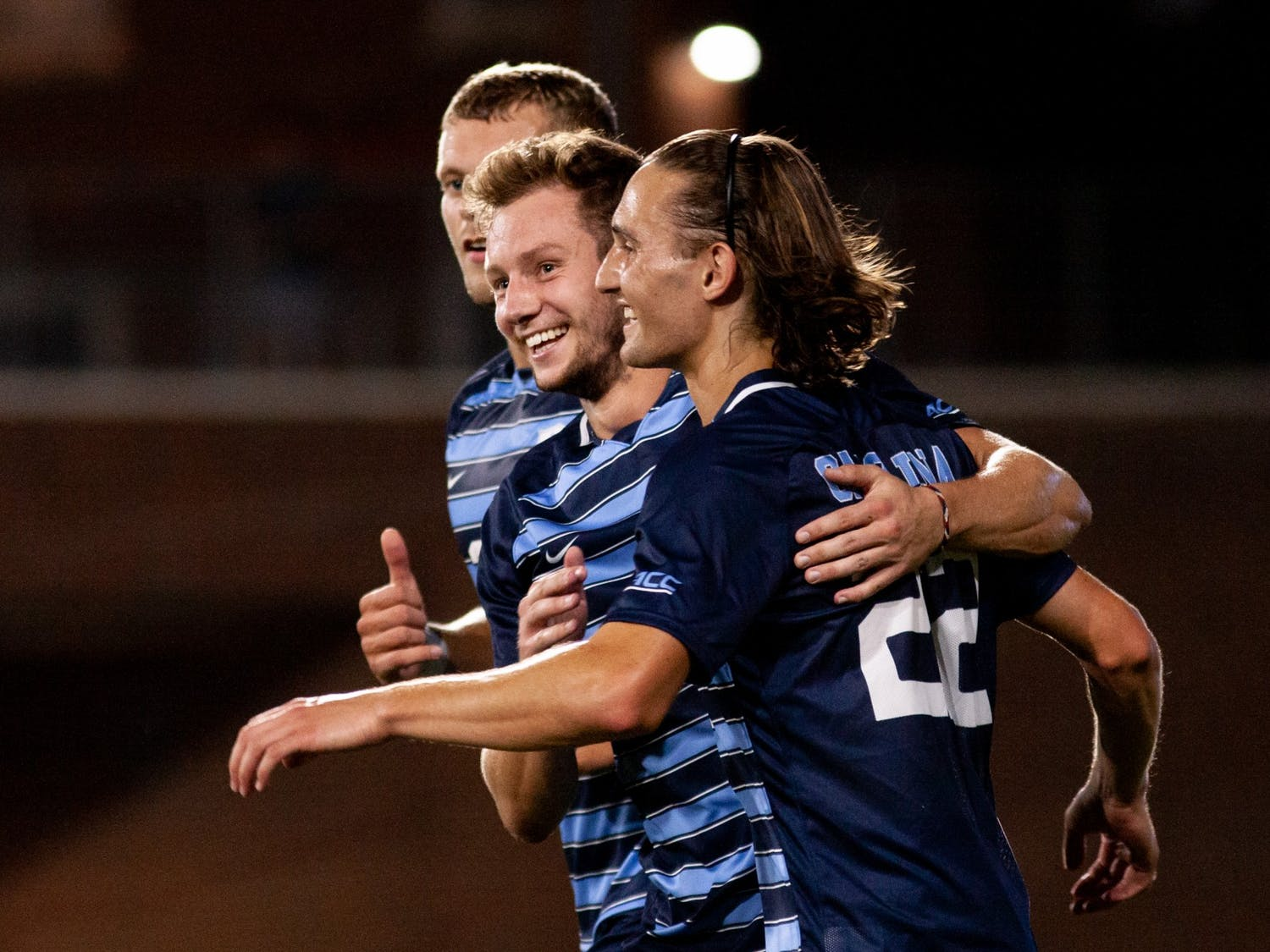 The UNC Tar Heels embrace after junior midfielder Cameron Fisher (17) scores the third goal of the game with an assist from midfielder/forward Ernest Bawa (20). The Tar Heels beat the Georgia Southern Eagles 3-0 at Dorrance Field on Friday, Sep. 3, 2021.
