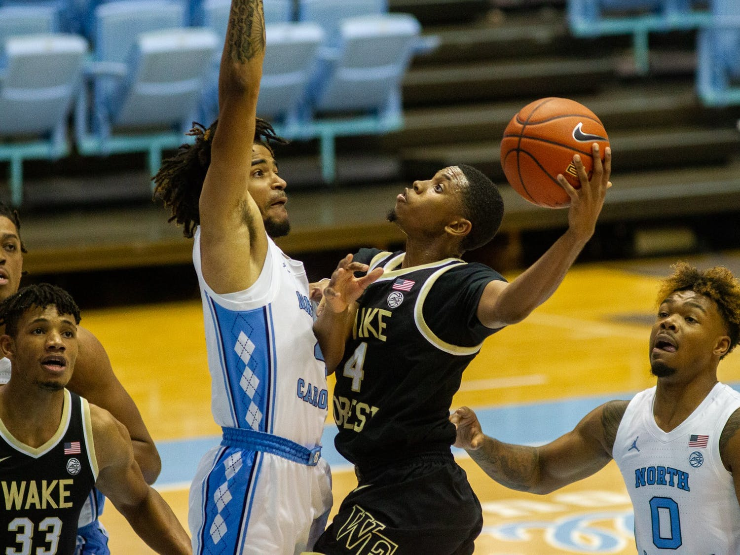 UNC freshman guard RJ Davis (4) defends against Wake Forest junior guard Daivien Williamson (4) in the Dean Smith Center Jan. 20, 2021. The Tar Heels beat the Demon Deacons 80-73.