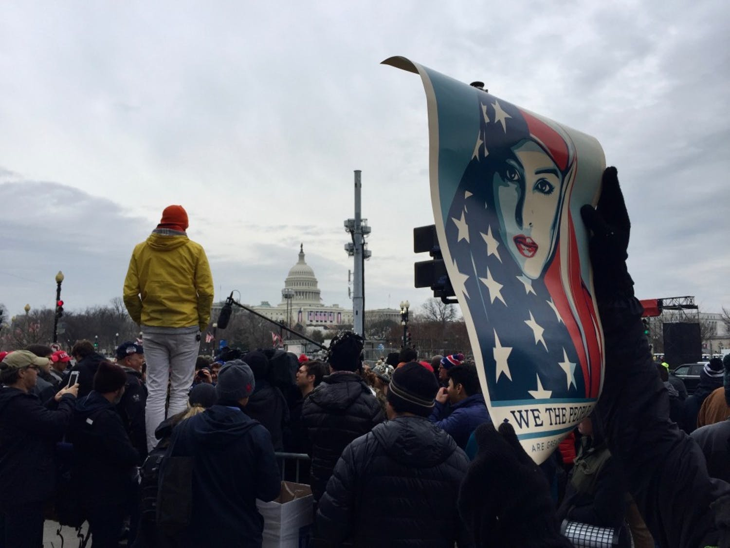 """A protester holds a sign — designed by Shepard Fairey —reading """"We the people are greater than fear."""" Fairey is the artist responsible for iconic 'Hope' photos of former President Barack Obama."""