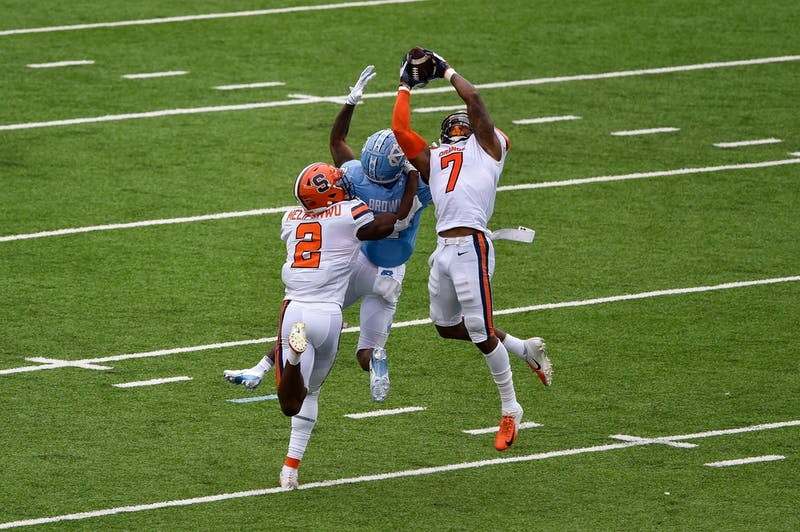 Syracuse junior defensive back Andre Cisco (7) nabs an interception from UNC junior wide reciever Dyami brown (2) with help from redshirt junior defensive back Ifeatu Melifonwu (2) during a game in Kenan Memorial Stadium on Saturday, Sept. 12, 2020. UNC beat Syracuse 31-6.