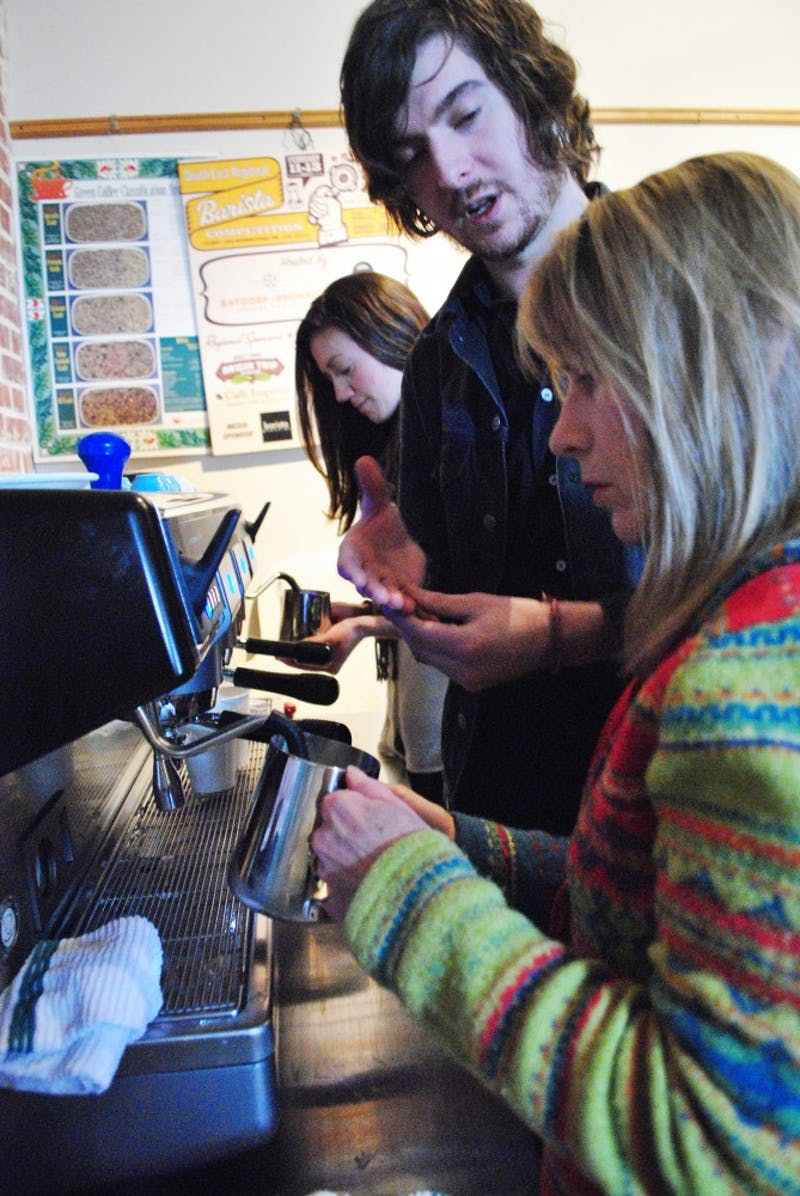 Open Eye barista, Miles Murray, teaches Candy Cooper how to steam milk and make latte designs on Saturday morning.