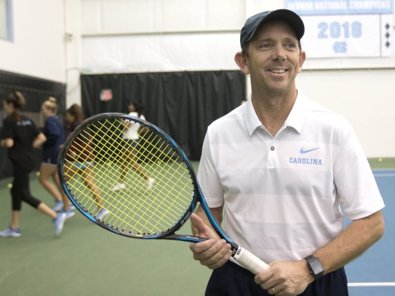Women's tennis Head Coach Brian Kalbas smiles as he chats with a colleague at the Cone-Kenfield Tennis Center on Wednesday, Jan. 30, 2019. Kalbas, a coach for the Tar Heels for 16 years, led his team to three ACC championships in a row from 2016-18 and was named ACC Coach of the Year five times. He holds a 602-180 career record, making him the winningest coach in ACC history and cementing him as leader in all-time wins at Carolina with 388-95.