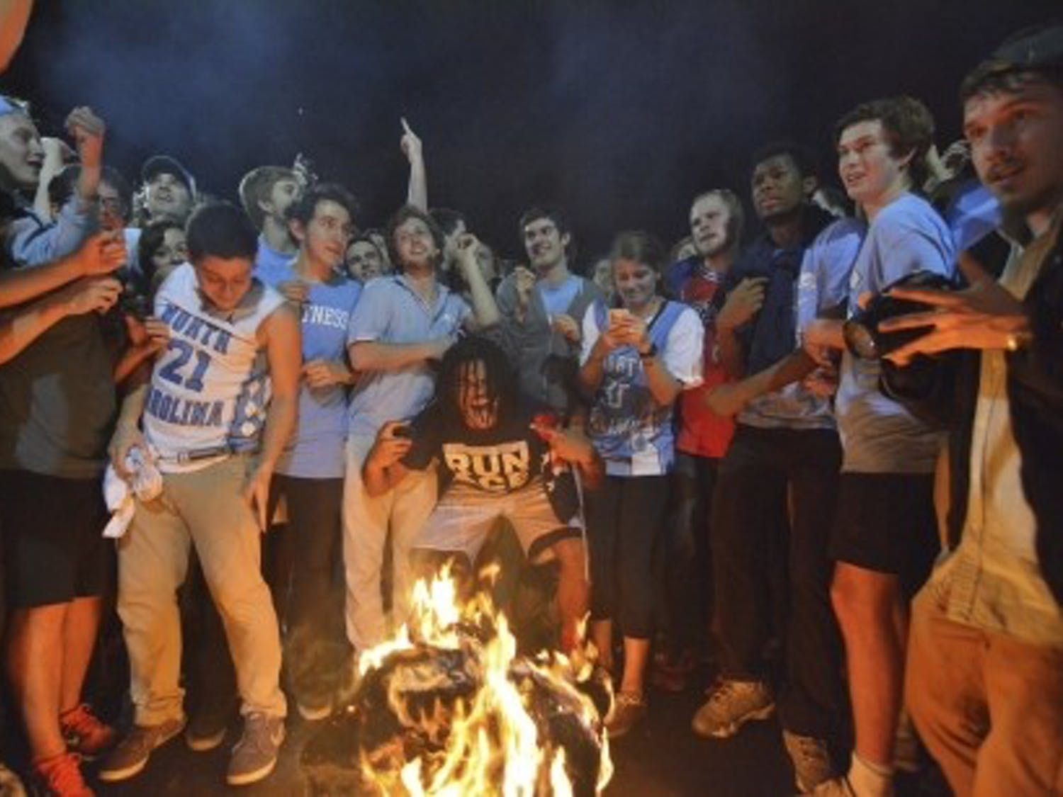 Excited fans jump over a bonfire on Franklin Street after North Carolina beats Duke in men's basketball.