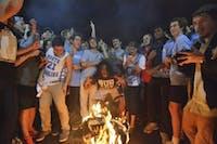 Excited fans jump over a bonfire on Franklin Street after North Carolina beats Duke in men's basketball.