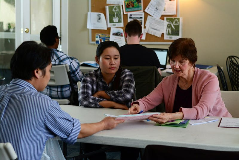 A refugee from Thailand (left) speaks with organizer Flicka Bateman (right) about papers while a translator (center) looks on.