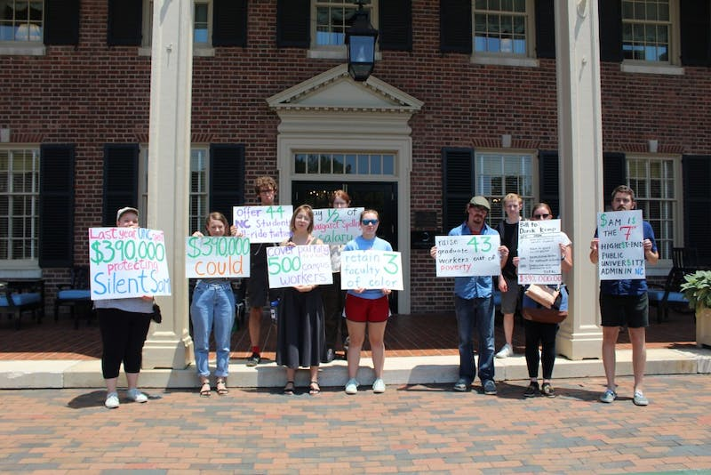 Protestors hold up signs in front of the Carolina Inn on July 18 protesting the Board of Trustees' expenditure on protecting Silent Sam.