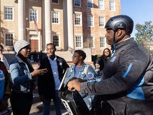 """(From left) UNC students De'Ivyion Drew, Tamia Sanders, Chris Suggs and Keoana Nettles lay out several grievances they have with UNC police to Chief Perry. These criticisms referenced officer turnout at public meetings, Chief Perry's demeanor and appearance at the protest, and police behavior at protests. UNC's Black Student Movement, Black Congress and student and local activists convened in McCorkle place before marching to South Building on Thursday, Dec. 5, 2019 at 1 p.m. The activists named the event """"Silent Sam is Not """"Resolved"""""""" and protested the University giving a $2.5 million trust fund to the Sons of Confederate Veterans and Silent Sam in a deal which removed Silent Sam from campus."""