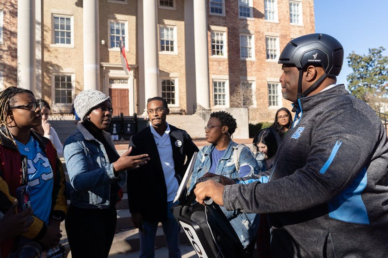 "(From left) UNC students De'Ivyion Drew, Tamia Sanders, Chris Suggs and Keoana Nettles lay out several grievances they have with UNC police to Chief Perry. These criticisms referenced  officer turnout at public meetings, Chief Perry's demeanor and appearance at the protest, and police behavior at protests. UNC's Black Student Movement, Black Congress and student and local activists convened in McCorkle place before marching to South Building on Thursday, Dec. 5, 2019 at 1 p.m. The activists named the event ""Silent Sam is Not ""Resolved"""" and protested the University giving a $2.5 million trust fund to the Sons of Confederate Veterans and Silent Sam in a deal which removed Silent Sam from campus."
