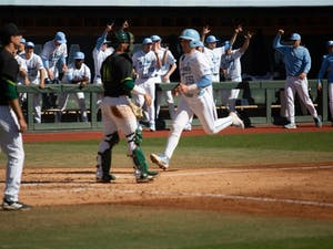 First-year infielder Michael Busch (23) scores the game tying run in the bottom of the third against USF on Sunday, Feb. 24, 2019 at Boshamer Stadium.
