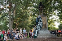 """Protesters drape a flag that reads """"Rest in Power: Heather Heyer"""" over the Silent Sam monument. Heyer was hit and killed by a car that drove into a crowd during the Charlottesville protests."""