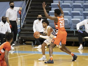 Syracuse's Robert Braswell (20) defends North Carolina's R.J. Davis (4) in the backcourt during the second half on Tuesday, January 12, 2021 at the Smith Center in Chapel Hill, NC. Photo courtesy of Robert Willett.