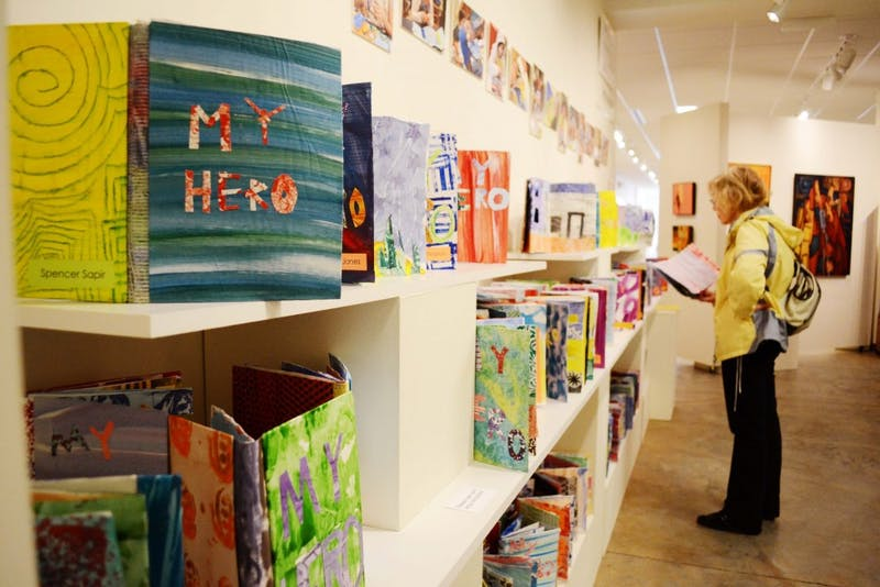 """FRANK gallery exhibit, """"Meet Our Heros"""" displays the work of Durham Academy 6th grade students. The students created pop-up books that tell the story of their heroes. Ridna Frasbergen looks at one of the books created by her grandson's classmate."""