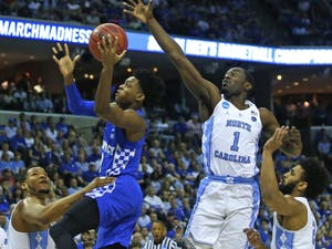 North Carolina wing Theo Pinson (1) attempts to swat the ball away from Kentucky guard D'Aaron Fox (0) in their Elite Eight matchup in Memphis on Sunday.