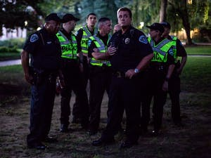 UNC Department of Public Safety Officers confer with one another on how to best handle protesters zip-tying large banners around Silent Sam on Aug. 20, 2018.