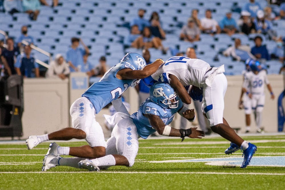 UNC junior defensive back Giovanni Biggers (27) and first year linebacker Power Echols (23) tackle a Georgia State player at the game on Sept. 11 at Kenan Stadium. UNC won 59-17.