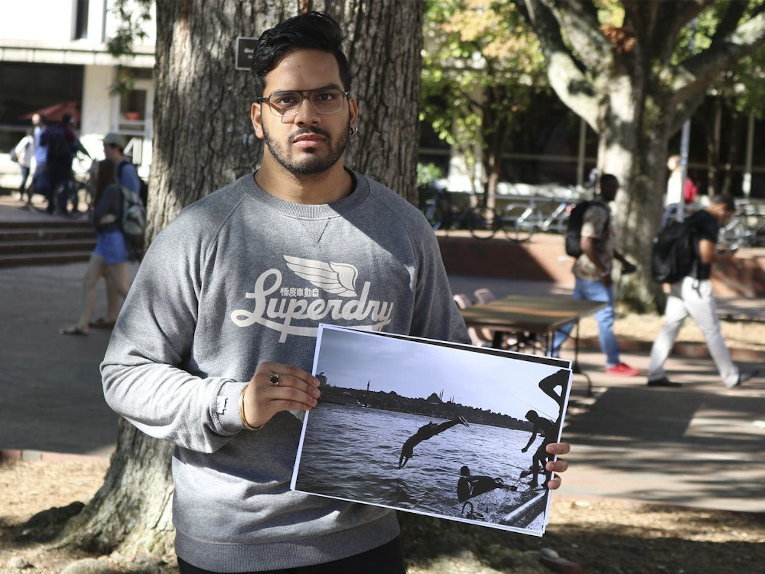 Arpan Bhandari, a religious studies and political science major,  displaying one of his photographs that are up for sale to raise money for syrian refugees. UN Refugee Agency
