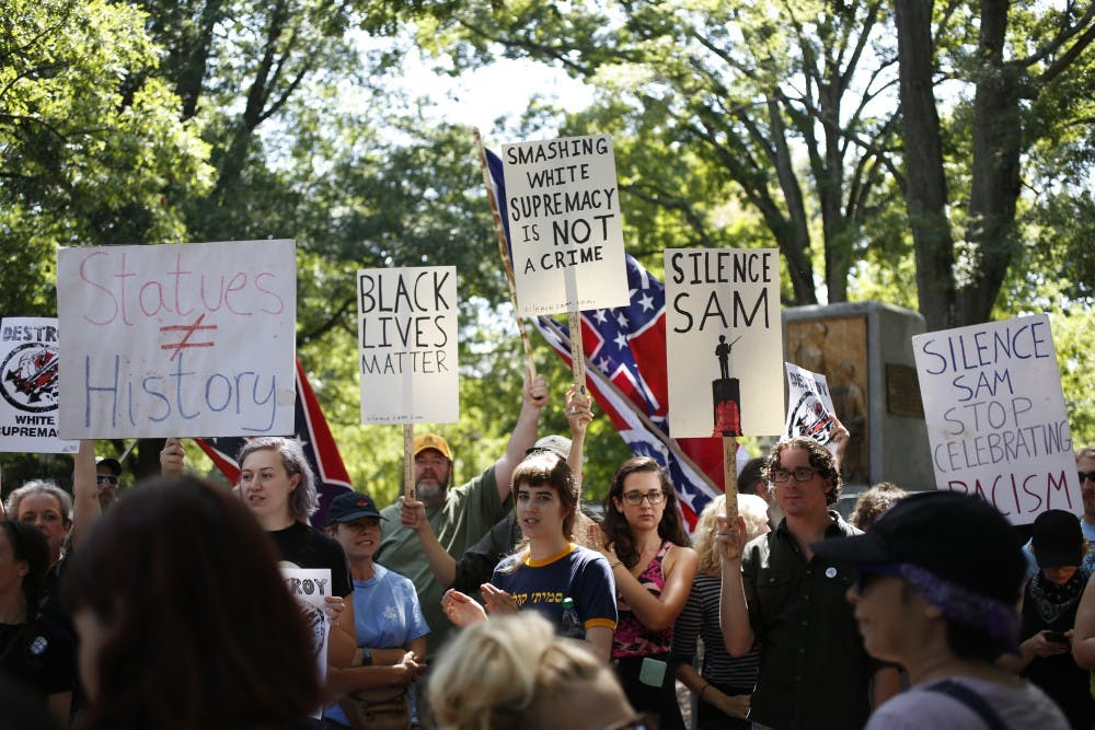 Demonstrators rally around what remains of Silent Sam on Saturday, August 25.