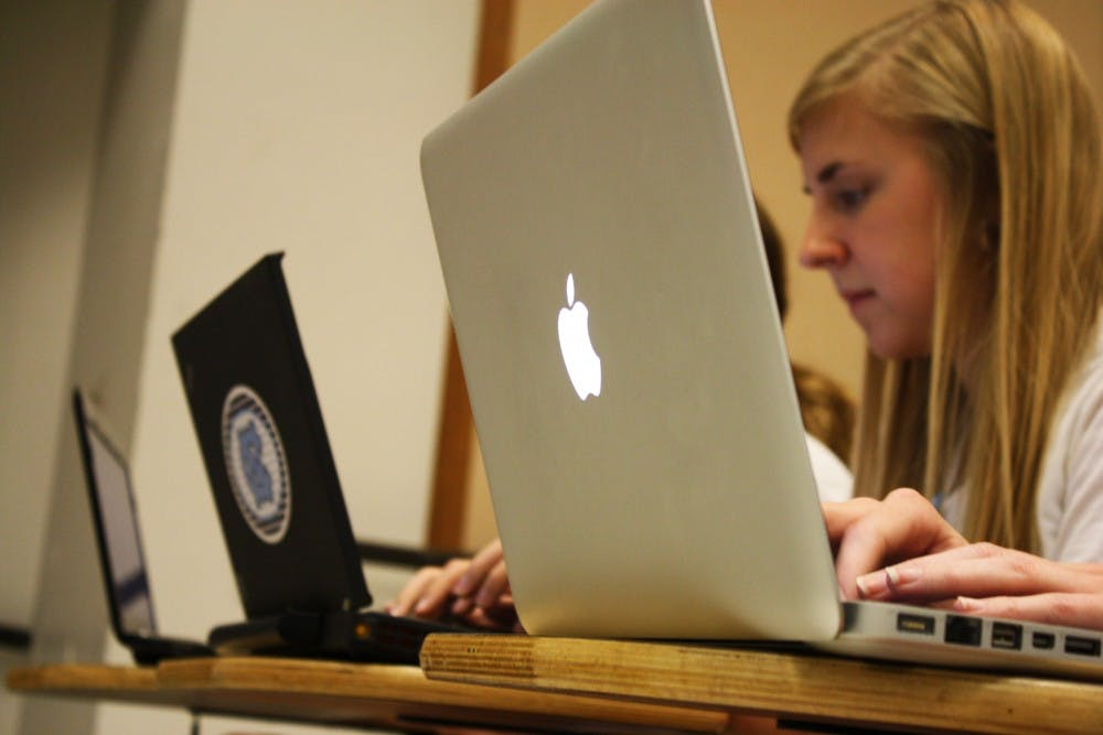 In Sociology 101, students type notes on their Thinkpad and Mac laptops. Beginning next year, the university will sell MacBook Pros as a part of the CCI program.girl pictured: freshman sociology major Erin Hancock