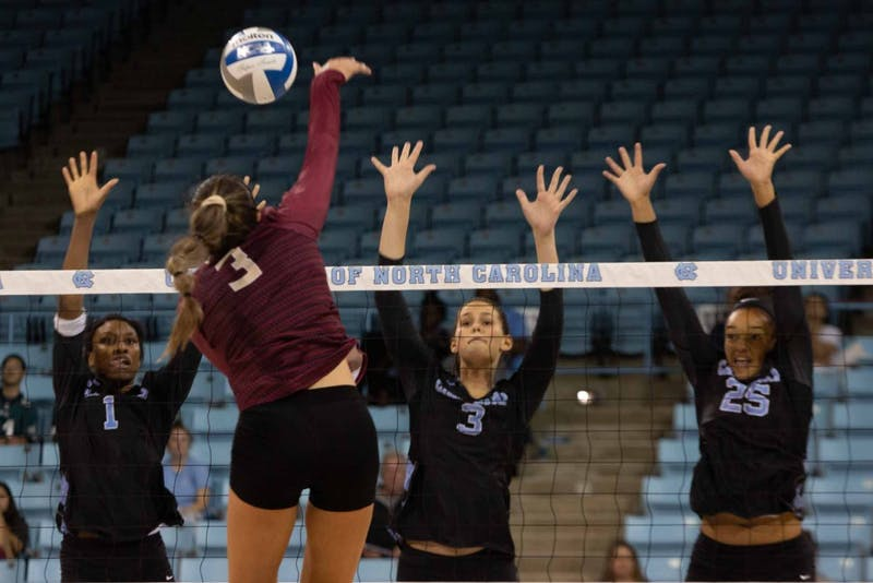 UNC sophomore outside hitter Destiny Cox (1), junior middle blocker Aristea Tontai (3) and redshirt first-year outside hitter Lauren Harrison (25) attempt to block the ball from Seminole first-year opposite hitter Kirstyn Anderson (3). UNC won against FSU 3-2 at Carmichael Arena on Sunday, Oct. 13, 2019.