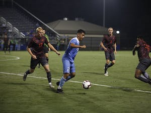 Sophomore Midfielder Raul Aguilera (28) fights to keep control of the ball against against Virginia Tech players during Saturday's game against Virginia Tech at Koskinen Stadium. UNC won 2-1.
