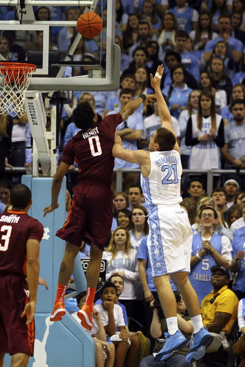 UNC senior forward Jackson Simmons (21) attempts a field goal, but is blocked by Virginia Tech junior forward Shane Henry (0).