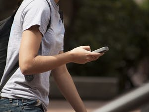 Junior chemistry major Emily Janeira walks and texts in front of Bingham on Wednesday.