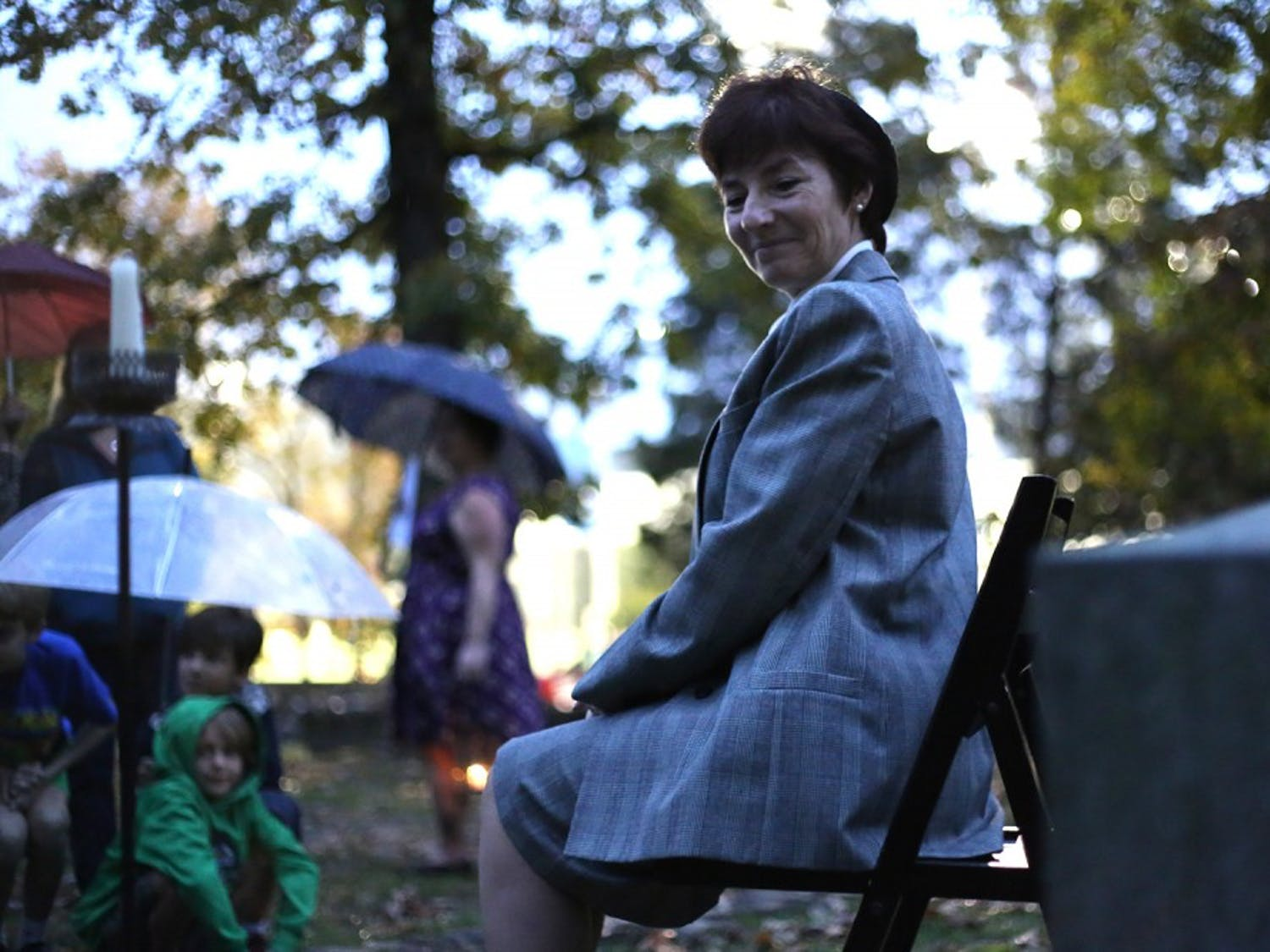 """Christine Rogers performs as Alma Holland Beers in front of Beers' grave in the Old Chapel Hill Cemetery Thursday night. She performed as part of """"Voices from the Grave: Haunted Cemetery Tours."""""""